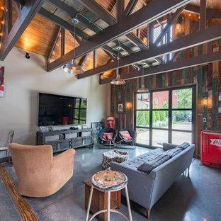 Ejemplo de sala de juegos en casa abierta, de estilo de casa de campo, sin chimenea, con paredes grises, suelo de cemento, televisor colgado en la pared y suelo gris