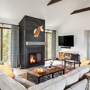 Diseño de sala de estar rústica con paredes blancas, suelo de madera clara, chimenea tradicional, televisor colgado en la pared, suelo beige y marco de chimenea de yeso