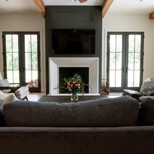 Ejemplo de sala de estar abierta, de estilo de casa de campo, con paredes beige, suelo de madera clara, chimenea tradicional, televisor colgado en la pared y marco de chimenea de madera