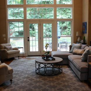 Imagen de sala de estar abierta, campestre, de tamaño medio, con paredes beige, suelo de madera en tonos medios, chimenea tradicional, marco de chimenea de piedra y televisor colgado en la pared
