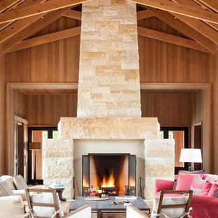 Ispirazione per un ampio soggiorno country aperto con pavimento in legno massello medio, cornice del camino in pietra e camino classico