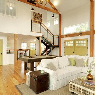 Immagine di un grande soggiorno country aperto con sala giochi, pareti bianche e pavimento in legno massello medio