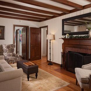 Imagen de sala de estar cerrada, de estilo de casa de campo, pequeña, con paredes beige, suelo de madera en tonos medios, chimenea tradicional, marco de chimenea de ladrillo y suelo marrón