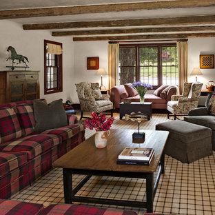 Imagen de sala de estar cerrada, campestre, grande, con paredes multicolor, suelo de madera en tonos medios, chimenea tradicional, marco de chimenea de piedra y televisor retractable
