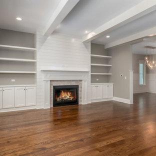 シカゴの中くらいのカントリー風おしゃれなオープンリビング (ライブラリー、グレーの壁、無垢フローリング、標準型暖炉、塗装板張りの暖炉まわり、埋込式メディアウォール、茶色い床、表し梁) の写真