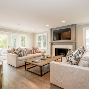 Imagen de sala de estar abierta, de estilo de casa de campo, de tamaño medio, con paredes grises, suelo de madera en tonos medios, chimenea tradicional, marco de chimenea de baldosas y/o azulejos y televisor colgado en la pared