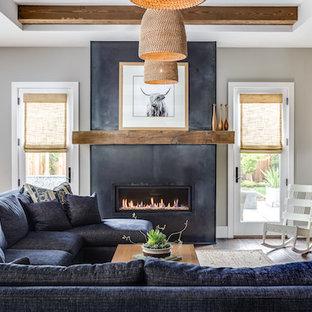 Diseño de sala de estar abierta, campestre, grande, con paredes grises, suelo de madera oscura, chimenea lineal, marco de chimenea de yeso y pared multimedia