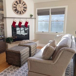 Diseño de sala de estar abierta, de estilo de casa de campo, grande, con paredes beige, suelo de madera en tonos medios, chimenea de esquina, marco de chimenea de yeso, televisor colgado en la pared y suelo marrón