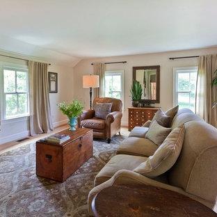 Imagen de sala de estar cerrada, de estilo de casa de campo, grande, sin chimenea, con suelo de madera clara, televisor independiente, paredes blancas y suelo beige