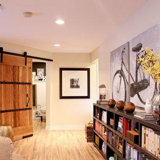 Réalisation d'une salle de séjour tradition de taille moyenne et fermée avec un mur jaune, un sol en bois clair, une cheminée standard, un manteau de cheminée en pierre et un téléviseur indépendant.