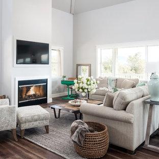 Imagen de sala de estar abierta, de estilo de casa de campo, con paredes grises, suelo de madera oscura, chimenea lineal y televisor colgado en la pared