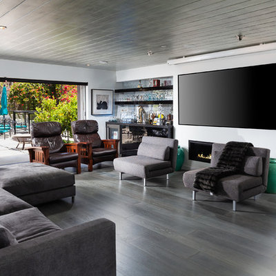 Family room - mid-sized contemporary enclosed dark wood floor and gray floor family room idea in Orange County with white walls, a wall-mounted tv, a bar, a ribbon fireplace and a metal fireplace