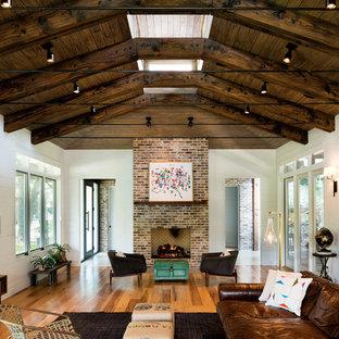 Imagen de sala de estar campestre con paredes blancas, suelo de madera en tonos medios, chimenea tradicional, televisor colgado en la pared y marco de chimenea de ladrillo
