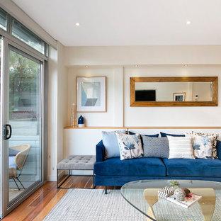 Fernseherloses, Offenes Retro Wohnzimmer ohne Kamin mit beiger Wandfarbe und Sperrholzboden in Sydney