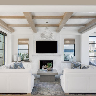 Family room - coastal open concept light wood floor family room idea in Orange County with white walls, a standard fireplace, a brick fireplace and a wall-mounted tv