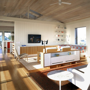 Inspiration for a beach style medium tone wood floor family room remodel in New York with white walls and a wall-mounted tv