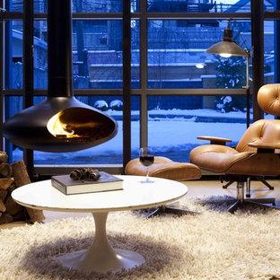 Imagen de sala de estar cerrada, actual, pequeña, con suelo de cemento y chimeneas suspendidas