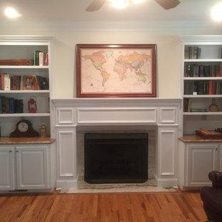 Imagen de sala de estar cerrada, pequeña, con chimenea tradicional y marco de chimenea de madera