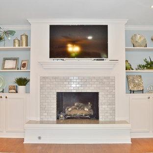 Modelo de sala de estar cerrada, tradicional renovada, pequeña, con paredes azules, suelo de madera clara, chimenea tradicional, marco de chimenea de baldosas y/o azulejos, televisor colgado en la pared y suelo marrón