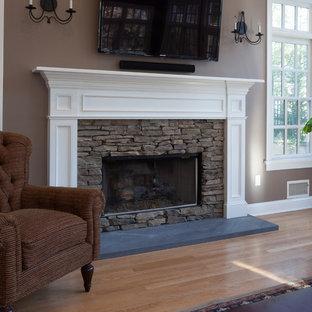 На фото: гостиная комната среднего размера в классическом стиле с паркетным полом среднего тона, стандартным камином, фасадом камина из камня, телевизором на стене и серыми стенами с