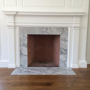 Imagen de sala de estar con biblioteca cerrada, clásica, de tamaño medio, con chimenea tradicional y marco de chimenea de madera