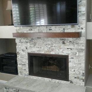 フェニックスの中サイズのトランジショナルスタイルのおしゃれなファミリールーム (ベージュの壁、カーペット敷き、横長型暖炉、石材の暖炉まわり、壁掛け型テレビ、グレーの床) の写真