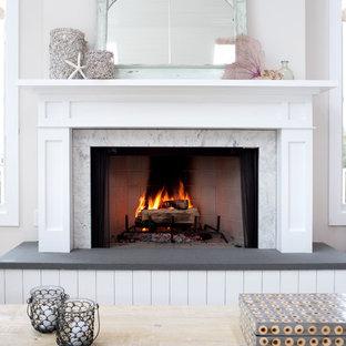 Inspiration pour une salle de séjour marine de taille moyenne et ouverte avec un mur beige, un sol en bois clair, une cheminée standard et un manteau de cheminée en bois.