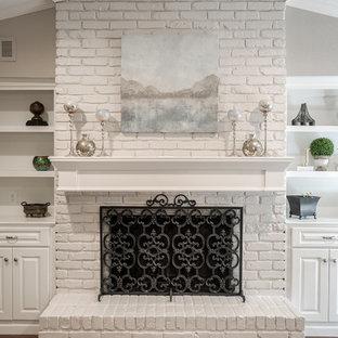 Ispirazione per un soggiorno tradizionale di medie dimensioni e chiuso con pareti grigie, pavimento in legno massello medio, camino classico, cornice del camino in mattoni e parete attrezzata