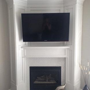 カルガリーの小さいトランジショナルスタイルのおしゃれなファミリールーム (コーナー設置型暖炉、壁掛け型テレビ、ベージュの床、グレーの壁、カーペット敷き、タイルの暖炉まわり) の写真