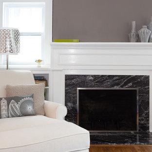 Inspiration pour une petit salle de séjour avec une bibliothèque ou un coin lecture vintage ouverte avec un mur gris, un sol en bois brun, une cheminée standard, un manteau de cheminée en pierre et un téléviseur dissimulé.