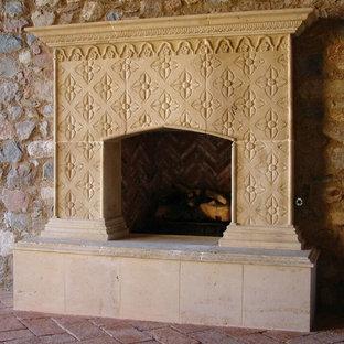 フェニックスの中サイズの地中海スタイルのおしゃれなファミリールーム (ベージュの壁、レンガの床、標準型暖炉、石材の暖炉まわり) の写真