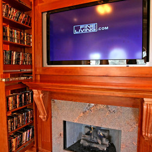 Example of a classic medium tone wood floor family room design in Atlanta with a standard fireplace, a wood fireplace surround and a media wall