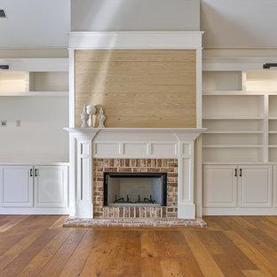 Immagine di un grande soggiorno chic con libreria, pareti bianche, pavimento in legno massello medio, camino classico, cornice del camino in mattoni e parete attrezzata