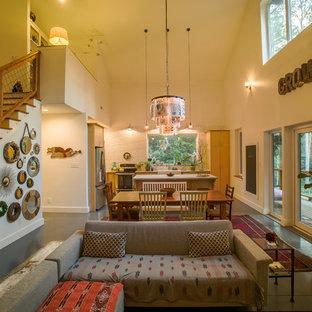 Foto de sala de estar tipo loft, de estilo de casa de campo, pequeña, sin chimenea, con paredes beige, suelo de cemento y televisor independiente