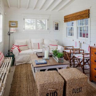 Imagen de sala de estar abierta, costera, pequeña, sin chimenea, con paredes blancas, suelo de madera clara y televisor colgado en la pared