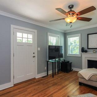 ローリーの小さいトラディショナルスタイルのおしゃれなファミリールーム (グレーの壁、無垢フローリング、標準型暖炉、レンガの暖炉まわり、据え置き型テレビ、茶色い床) の写真