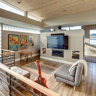 Foto di un soggiorno minimal di medie dimensioni e stile loft con pareti beige, pavimento in legno massello medio, camino lineare Ribbon, cornice del camino in metallo e TV a parete