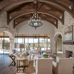 Стильный дизайн: огромная открытая гостиная комната в средиземноморском стиле с бежевыми стенами, светлым паркетным полом, стандартным камином, фасадом камина из камня и телевизором на стене - последний тренд
