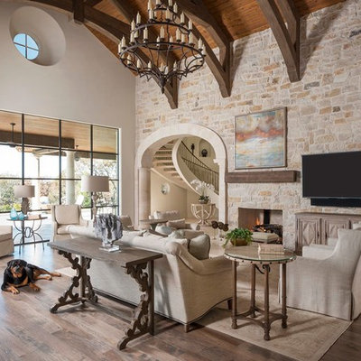 Family room - huge mediterranean medium tone wood floor family room idea in Dallas with a standard fireplace, a stone fireplace and a wall-mounted tv