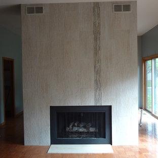 シカゴの大きいトランジショナルスタイルのおしゃれなファミリールーム (青い壁、無垢フローリング、両方向型暖炉、金属の暖炉まわり) の写真