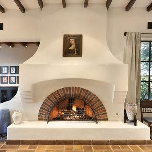 フェニックスの広いサンタフェスタイルのおしゃれなファミリールーム (白い壁、標準型暖炉、レンガの暖炉まわり) の写真