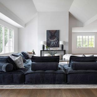 Exemple d'une très grande salle de séjour mansardée ou avec mezzanine chic avec un mur blanc, un sol en bois brun et un sol marron.