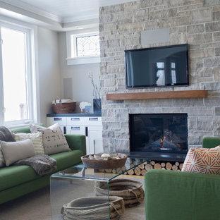 Ispirazione per un soggiorno chic di medie dimensioni con pareti grigie, camino classico, cornice del camino in pietra, TV a parete e moquette