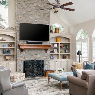 Ispirazione per un grande soggiorno chic aperto con pareti beige, pavimento in ardesia, camino classico, cornice del camino in pietra, TV a parete e pavimento multicolore
