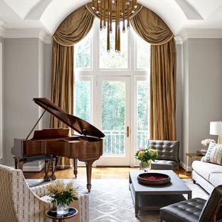Imagen de sala de estar con rincón musical tradicional, grande, sin televisor, con suelo de madera en tonos medios, chimenea tradicional, marco de chimenea de piedra y paredes grises