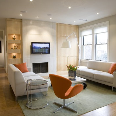 Inspiration for a contemporary medium tone wood floor family room remodel in DC Metro with beige walls, a standard fireplace and a wall-mounted tv