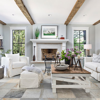 Inspiration for a mid-sized coastal multicolored floor family room remodel in Detroit with gray walls, a standard fireplace, a plaster fireplace and no tv