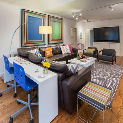 Family room - large eclectic enclosed medium tone wood floor family room idea in Dallas with white walls and a media wall
