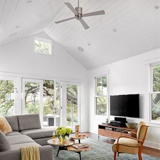 Ejemplo de sala de estar de estilo de casa de campo, sin chimenea, con paredes blancas, suelo de madera oscura y televisor colgado en la pared