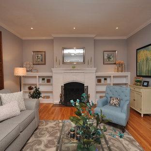 オタワの大きいコンテンポラリースタイルのおしゃれな独立型ファミリールーム (グレーの壁、無垢フローリング、標準型暖炉、レンガの暖炉まわり、埋込式メディアウォール) の写真